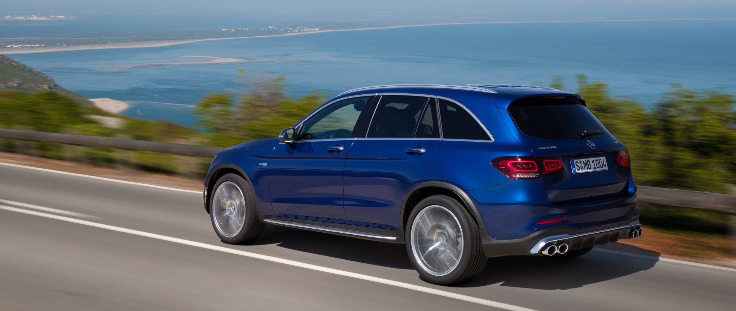 The 2019 Mercedes-AMG GLC 43 4MATIC SUV (X 253) in brilliant blue: rear view on a coastal road.