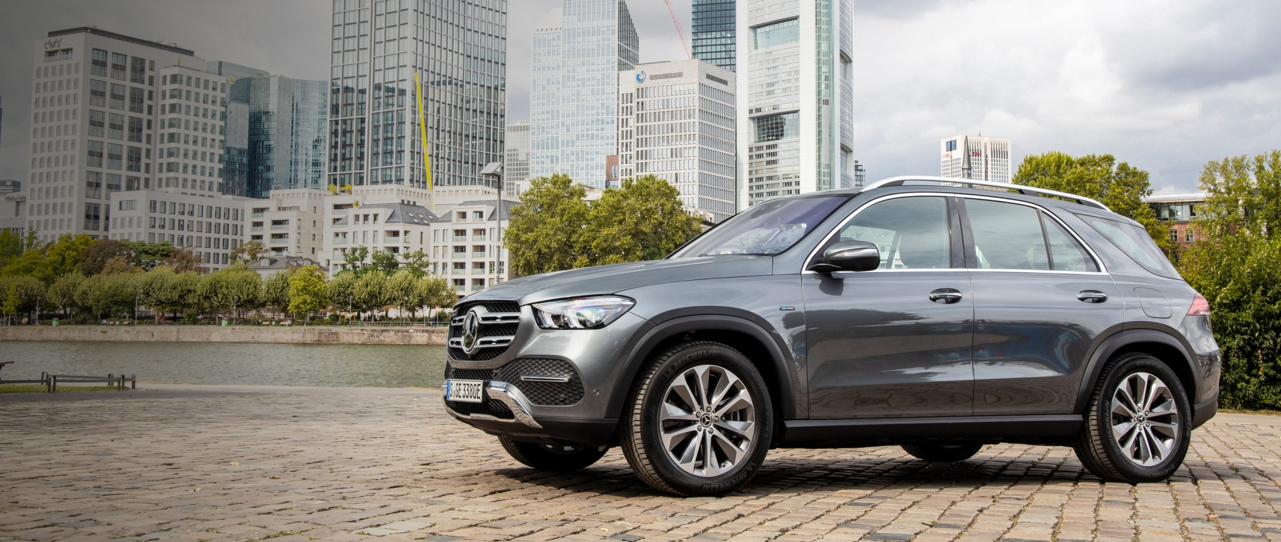 The new plug-in hybrid Mercedes-Benz GLE 350 de 4MATIC (W 167) in selenite grey in front of a skyline.