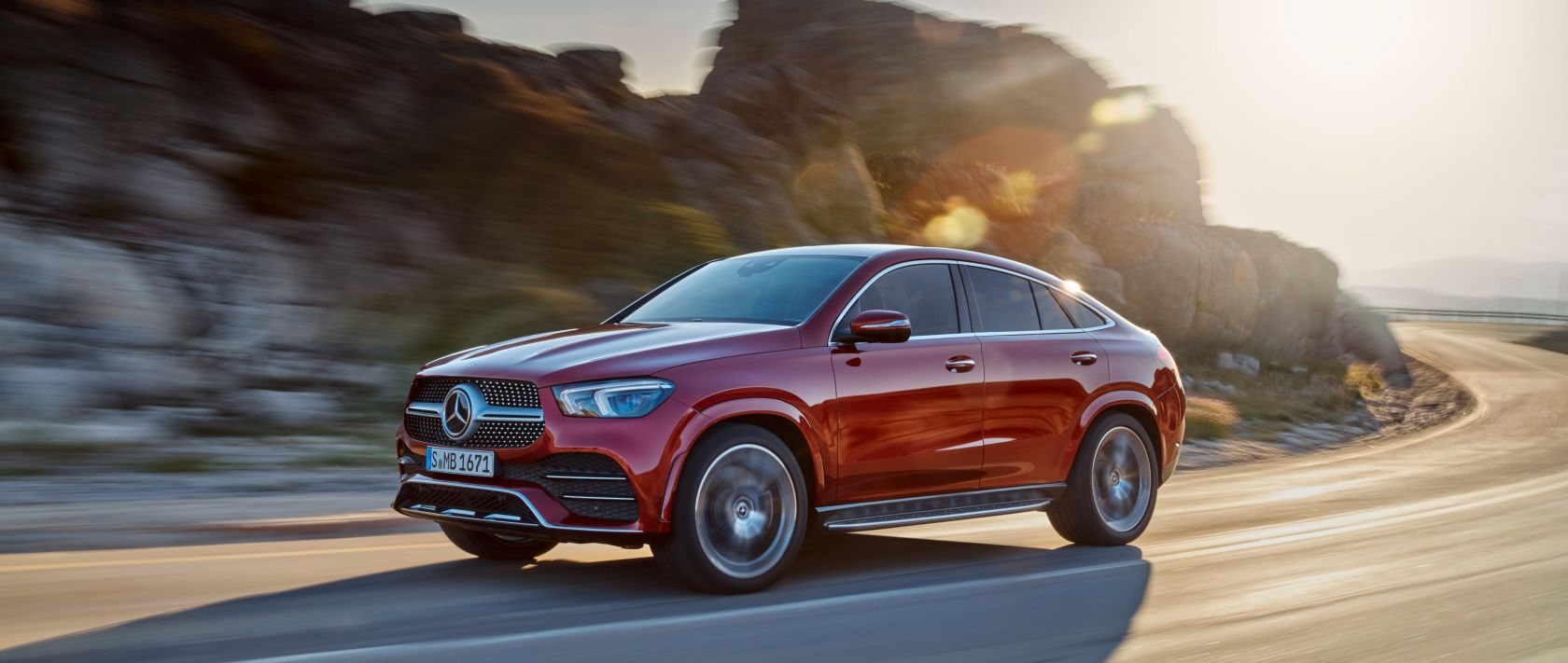 The new 2020 Mercedes-Benz GLE Coupé (C 167) in designo hyacinth red metallic at sunset on a country road.