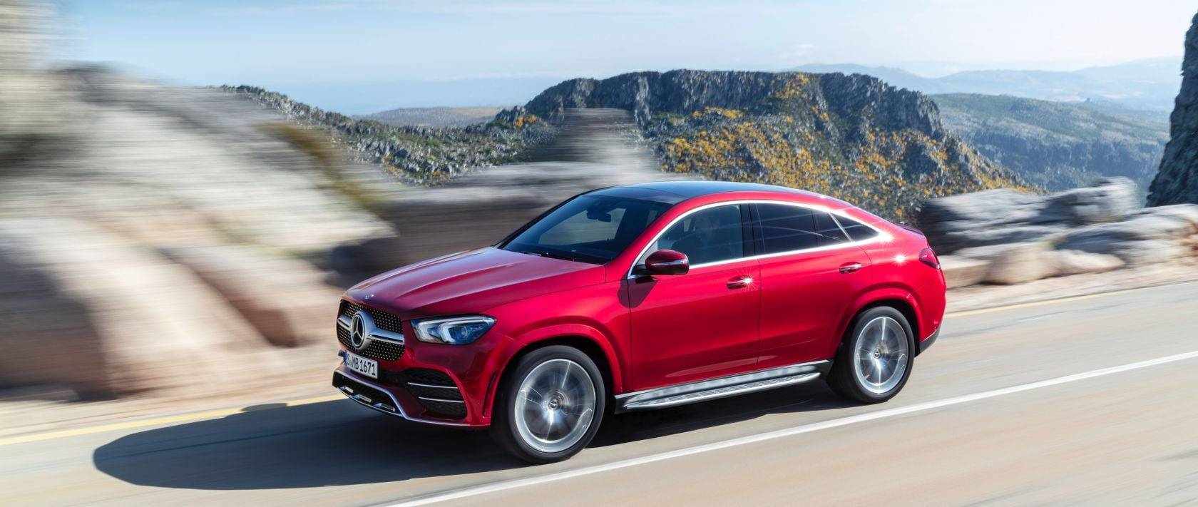 Side view of the new 2020 Mercedes-Benz GLE Coupé (C 167) in designo hyacinth red metallic on a country road.