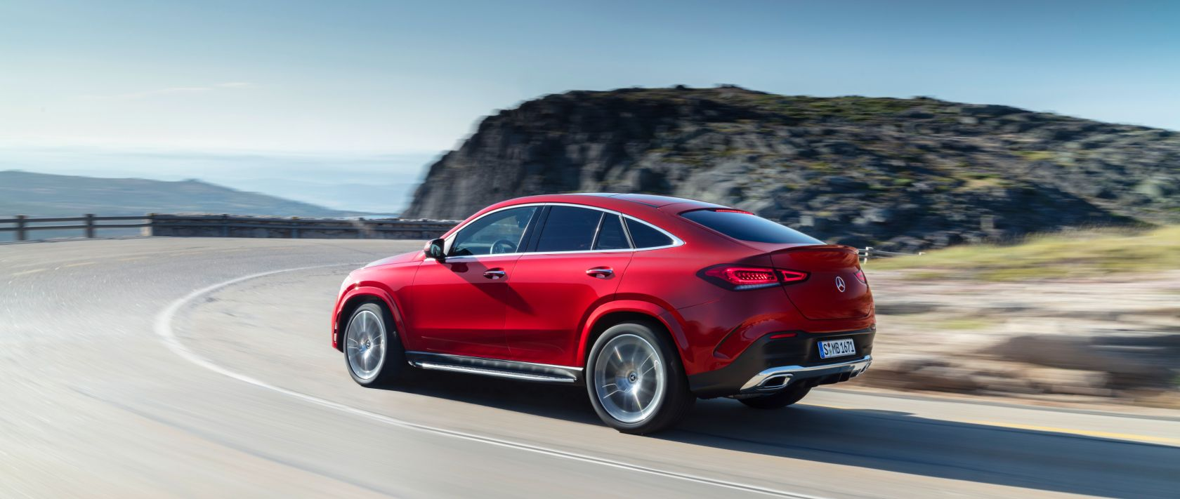 Rear view of the new 2020 Mercedes-Benz GLE Coupé (C 167) in designo hyacinth red metallic on a country road.