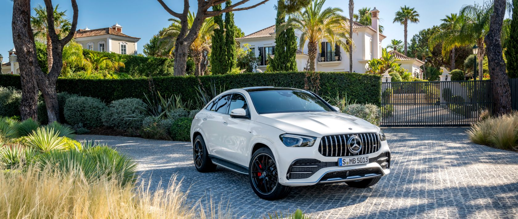 The new 2020 Mercedes-AMG GLE 53 4MATIC+ Coupé (C 167) in designo diamond white bright surrounded by palm trees.