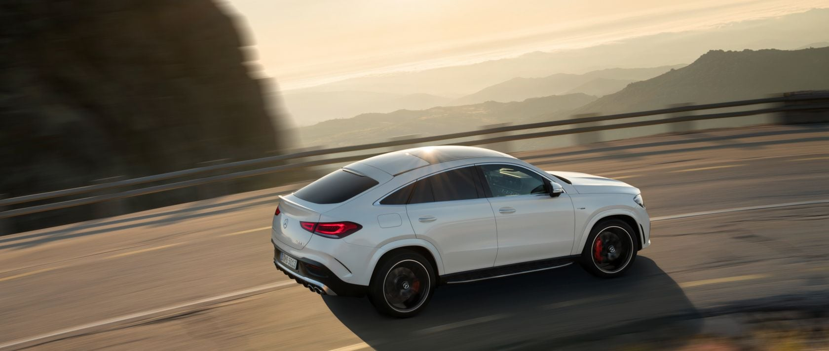 Side view: The new 2020 Mercedes-AMG GLE 53 4MATIC+ Coupé (C 167) in designo diamond white bright on a country road.