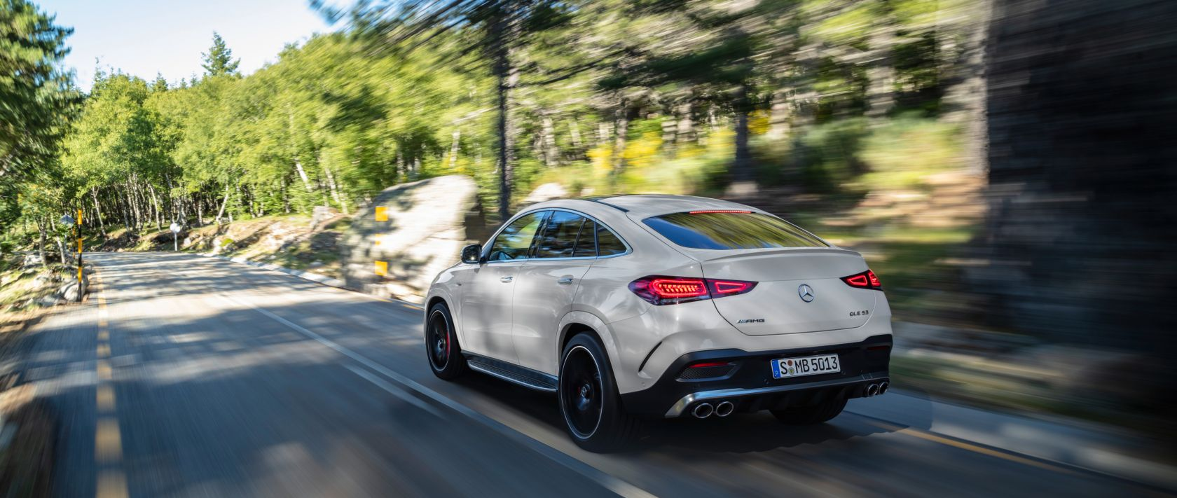 Rear view: The new 2020er Mercedes-AMG GLE 53 4MATIC+ Coupé (C 167) in designo diamond white bright on a country road.