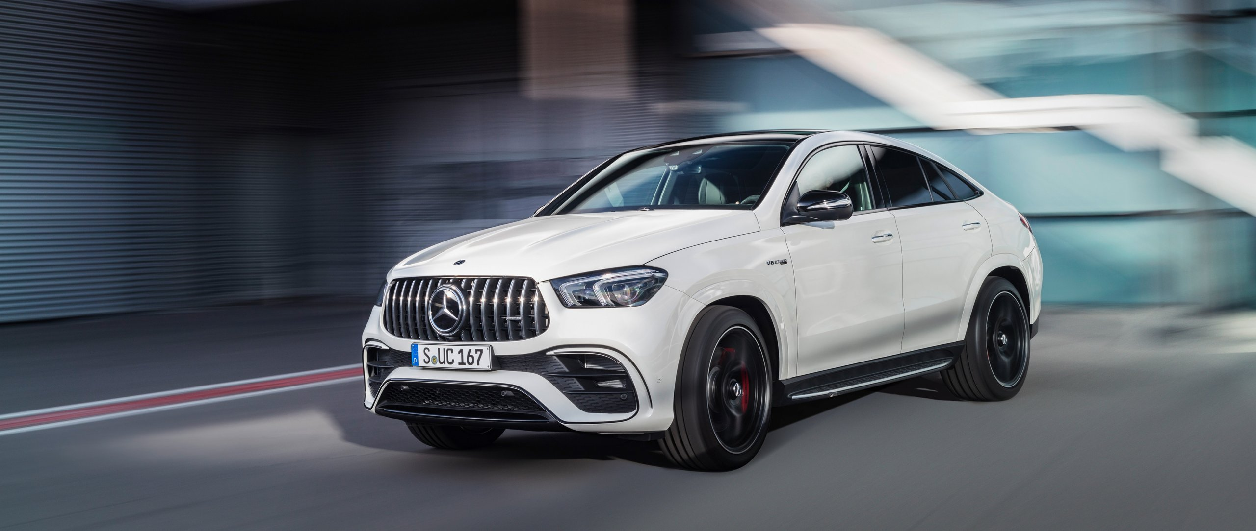 The new Mercedes-AMG GLE 63 S 4MATIC+ Coupé drives on a road. A blurred building can be seen in the background.