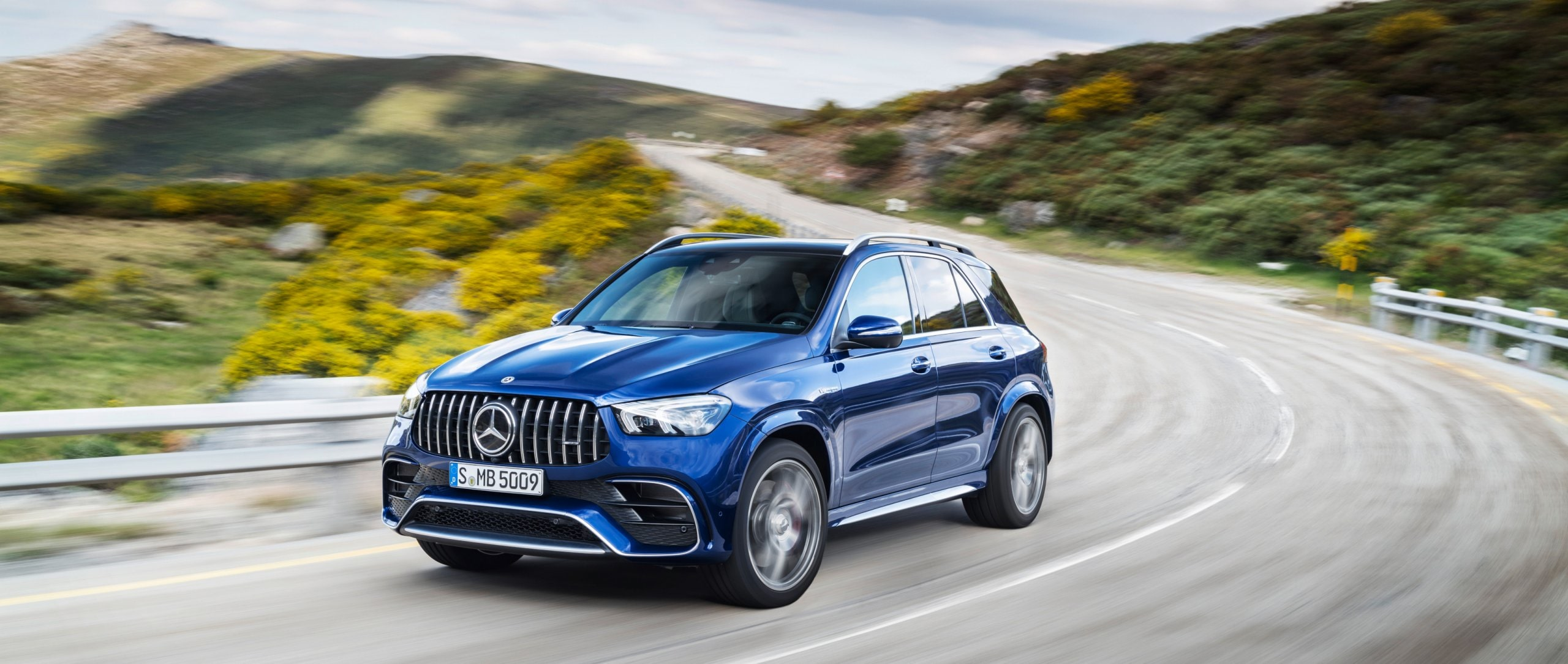 Front view: The new 2020 Mercedes-AMG GLE 63 S 4MATIC+ (W 167) in galaxy blue driving on a country road.
