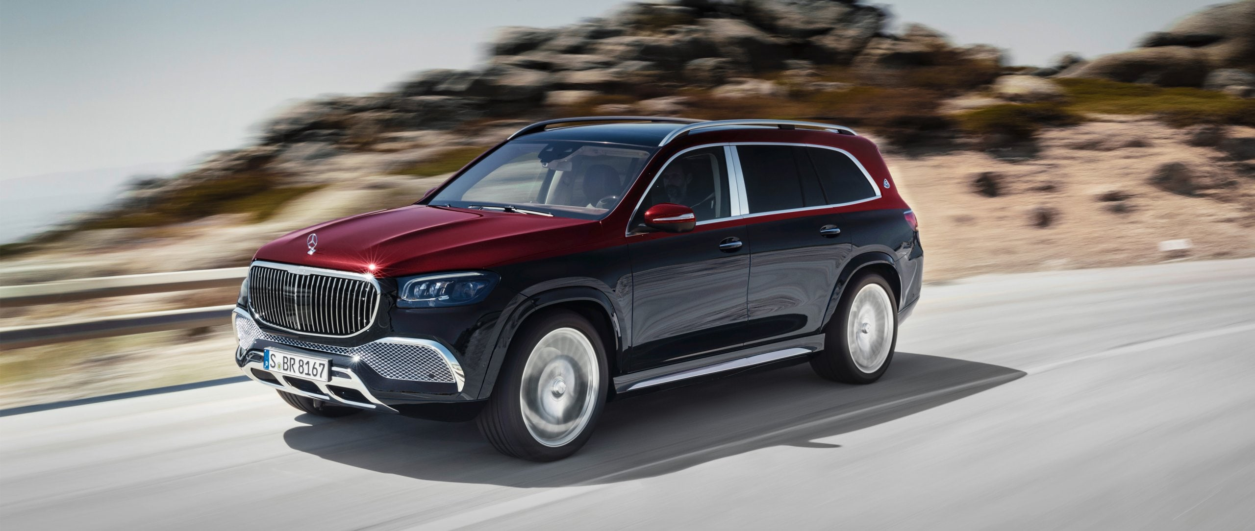 The new 2020 Mercedes-Maybach GLS 600 4MATIC (X 167) in the two-colour paint rubellite red/obsidian black on a country road.