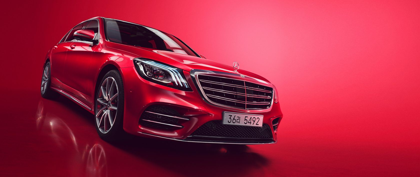 The Mercedes-Benz S 560 4MATIC in red with background.