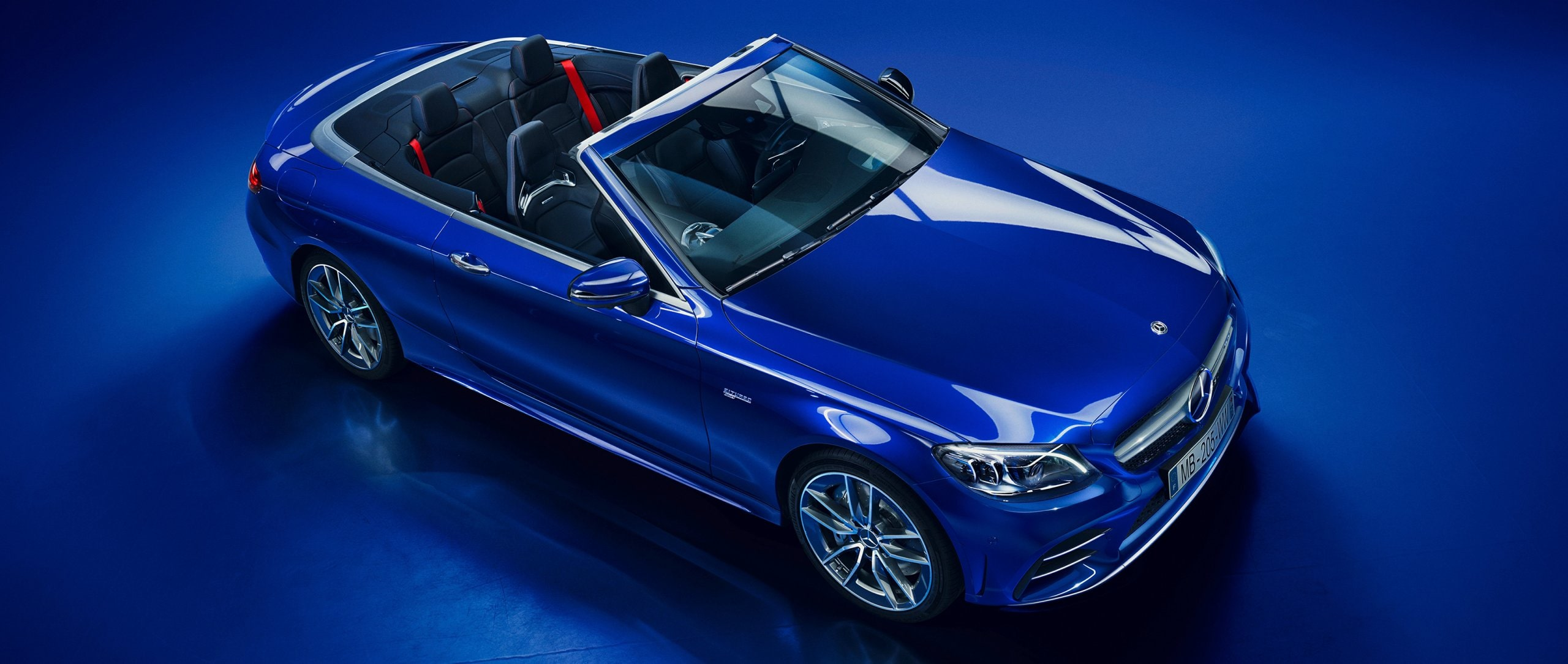 The Mercedes-AMG C 43 4MATIC Cabriolet in blue with blue background.