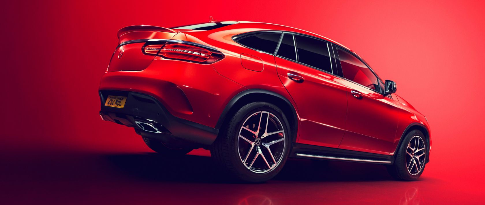 The Mercedes-Benz GLE 350 d 4MATIC Coupé in red with red background.