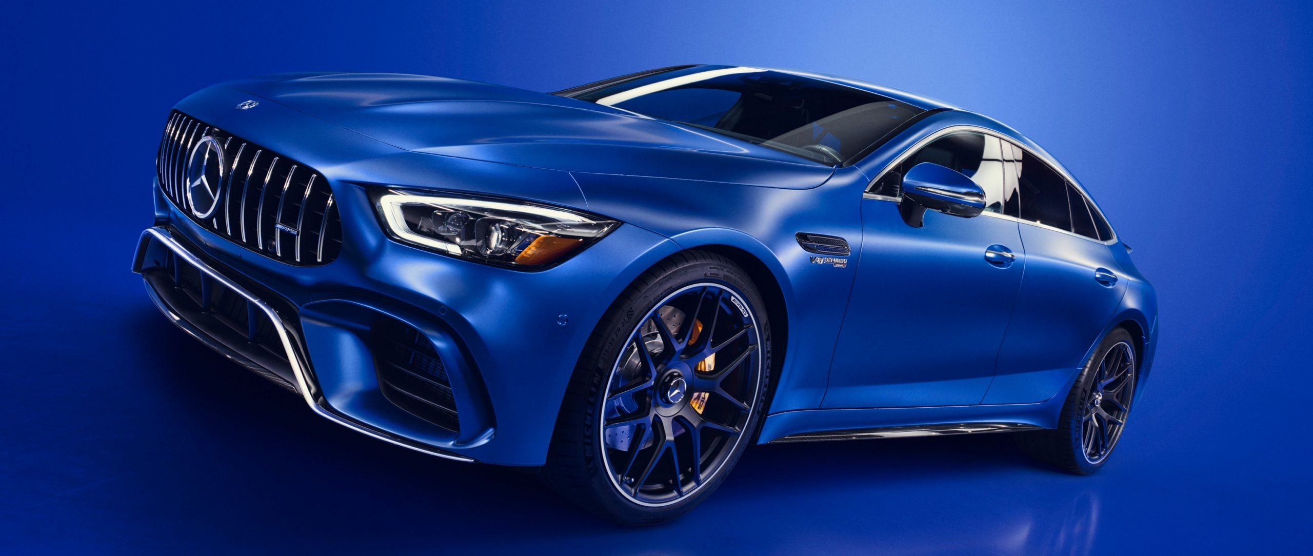 The Mercedes-AMG GT 63 S 4MATIC+ in designo brilliant blue magno with blue background.