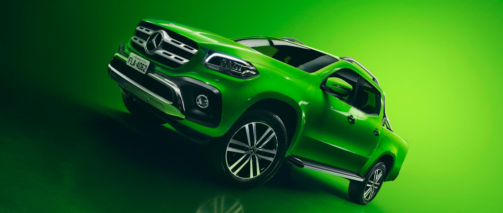 The Mercedes-Benz X 250 d 4MATIC in green with green background.