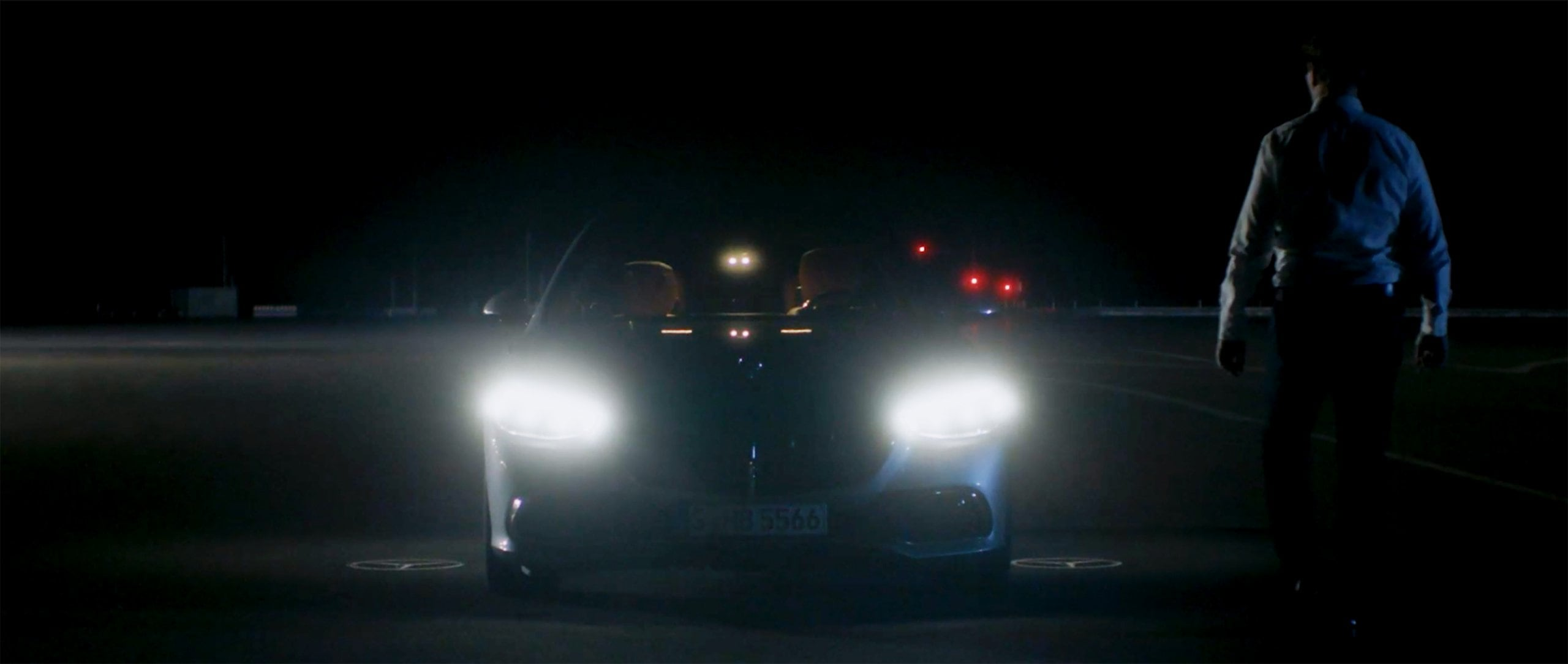 Ola Källenius walks towards the 2020 Mercedes-Benz S-Class at night.