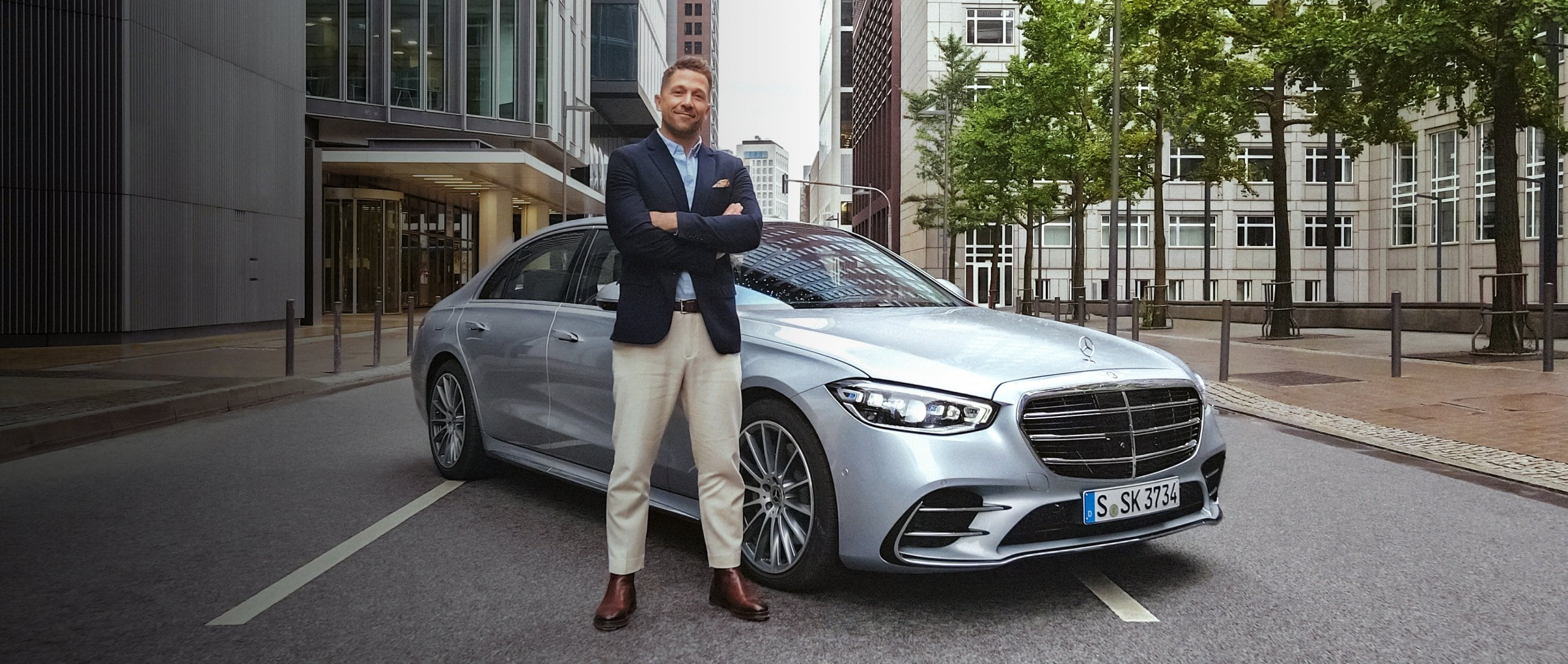 Florian Ambrosius stands in front of the new Mercedes-Benz S-Class (2020). Skyscrapers can be seen in the background.