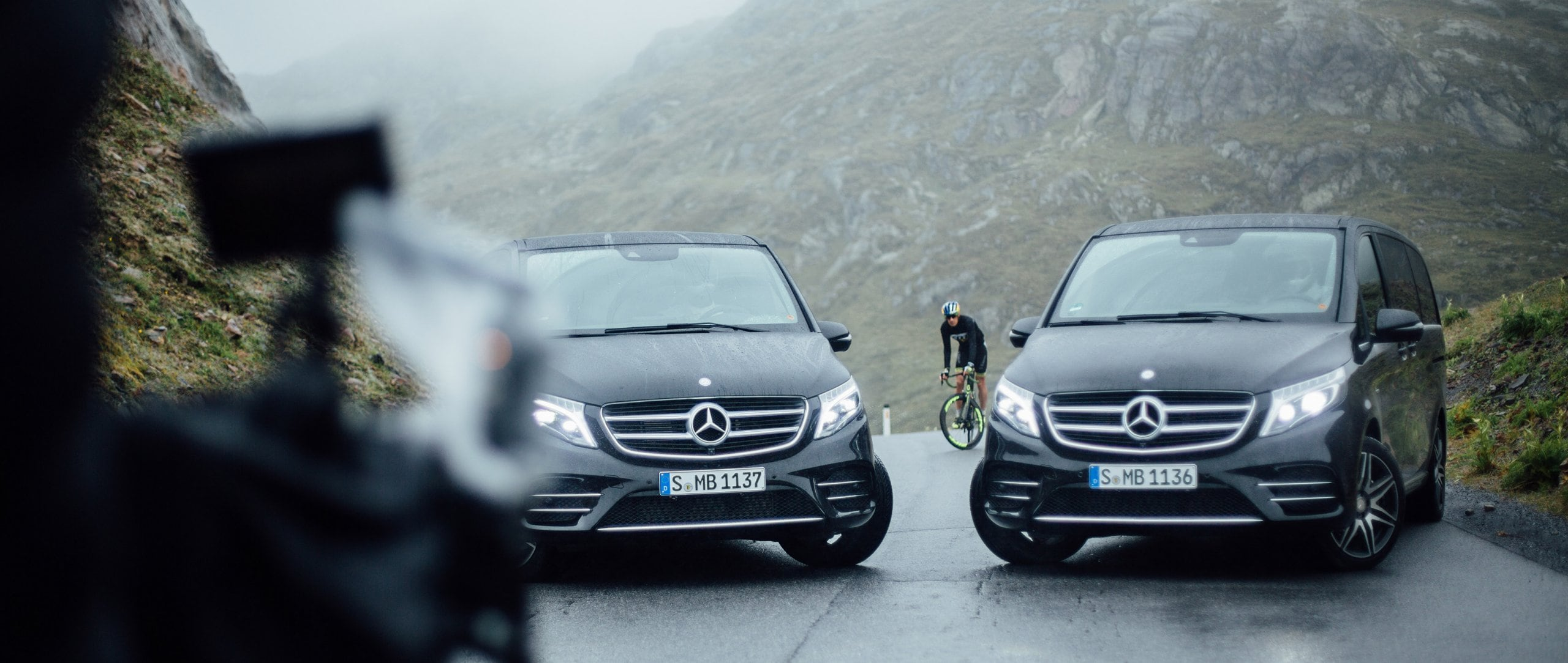 During a ride on his racing bike, Sebastian Kienle finds his way blocked by two Mercedes-Benz V-Class vehicles.