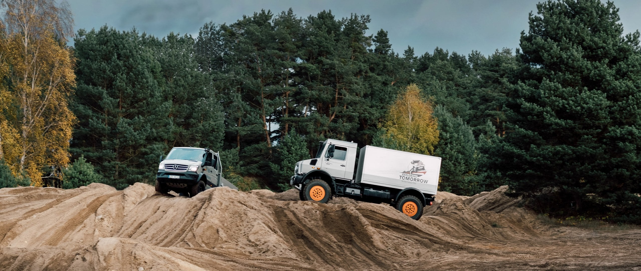A Mercedes-Benz Sprinter 6x6 and a Unimog drive in off-road terrain over hills.
