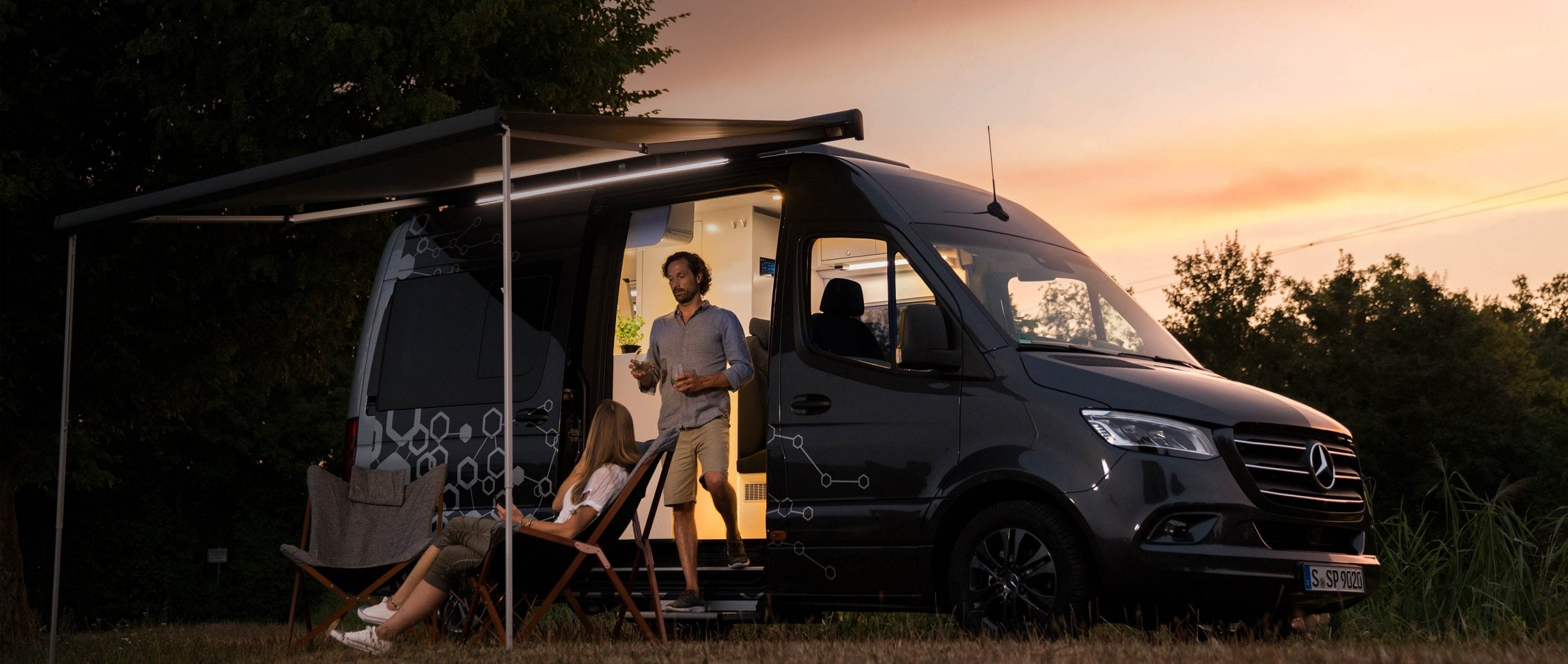 A young couple camps in a Mercedes-Benz Sprinter with a romantic sunset in the background